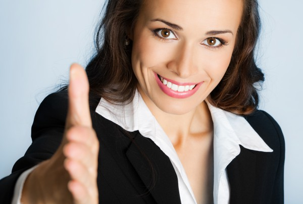Portrait of young cheerful beautiful business woman giving hand for handshake, over blue background