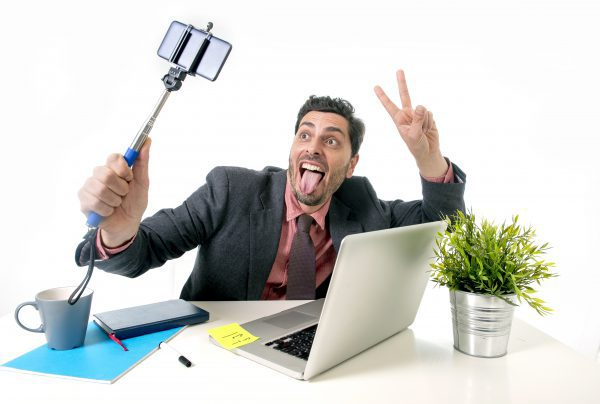 young attractive businessman in suit and tie working at office desk taking selfie photo with mobile phone camera and stick posing crazy happy and successful isolated on white background
